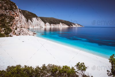 Fteri beach, Kefalonia, Greece. Lonely tourists protected from sun umbrella chill relax near clear