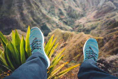 Feet of traveler streching down his legs over breathtaking mountain landscape with mountain peaks