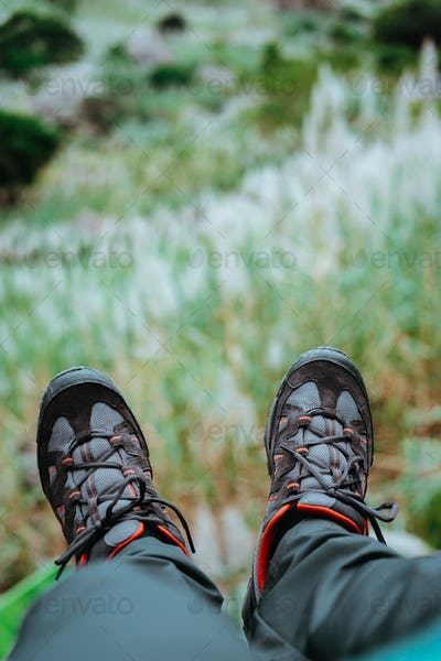 Hanging feet with trekking footwear over hill with sugarcane plants. Santo Antao Island, Cape Verde