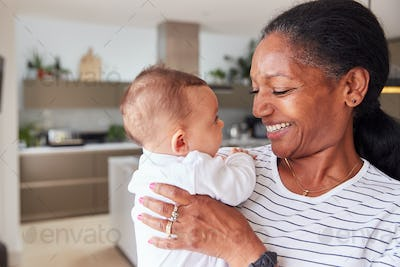 Loving Grandmother Holding 3 Month Old Baby Granddaughter In Kitchen At Home