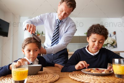 Businessman Father In Kitchen Brushing Hair And Helping Children With Breakfast Before School