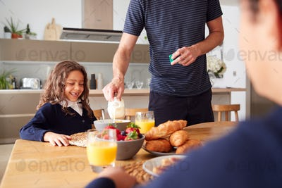 Father In Kitchen Helping Children With Breakfast Before Going To School