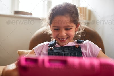 Girl Sitting In Armchair At Home Playing With Digital Tablet