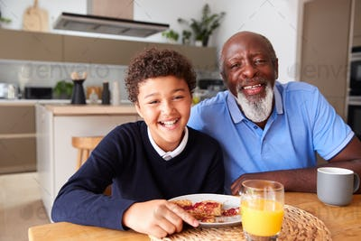 Portrait Of Smiling Grandfather Sitting In Kitchen With Grandson Eating Breakfast Before School