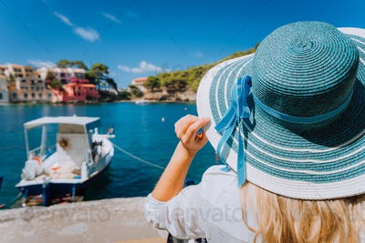 Happy young woman holding straw hat enjoying vacations in Assos village in front of emerald bay of