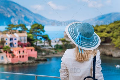 Tourist woman in blue sunhat on view point platform admire view of colorful tranquil village Assos