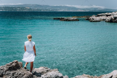 Jung adult women in white dress on summer vacation in front of sea coast landscape of small beach