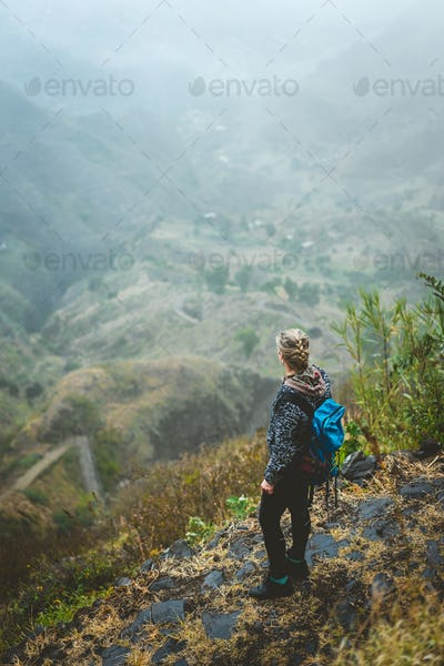 Traveler on cobbled path admiring spectacular lush green valley. Santo Antao island in Cabo Verde