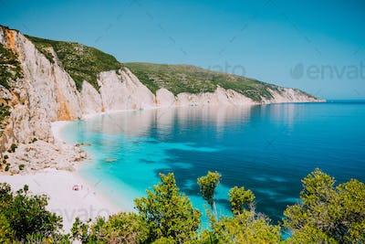 Sunny Fteri beach lagoon with rocky coastline, Kefalonia, Greece. Tourists under umbrella chill