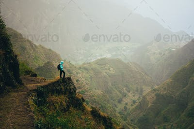 Hiker with backpack on the mountain top. Rocky terrain of a incredible panorama view of high