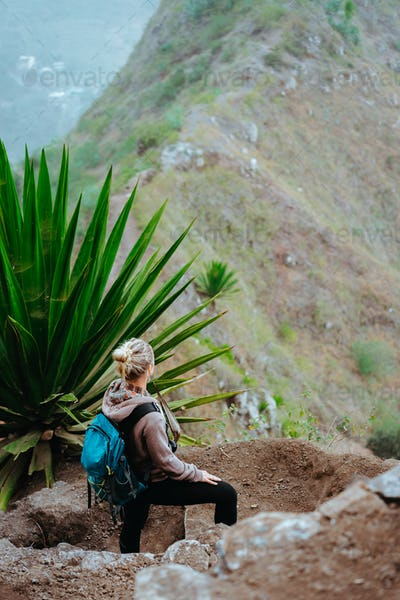 Woman with backpack on the trekking route near mountain edge looking down to valley. Santo Antao