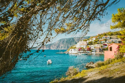 Pine tree grove branch frame view of Mediterranean sea bay in colorful Assos village. Kefalonia