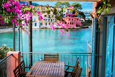Lilac fuchsia blossom flower over hotel veranda in front of turquoise colored bay of Mediterranean