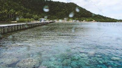 Wooden jetty near Yenbuba village leading to Mansuar island in Raja Ampat. Beautiful corals in