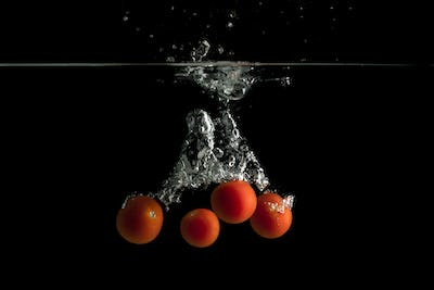 Four small tomatoes falls under water with splash