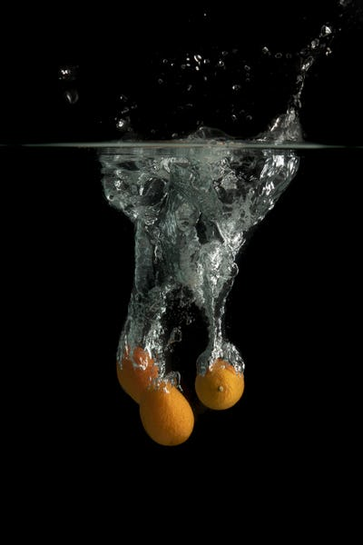 Three kumquat falls under water with splash