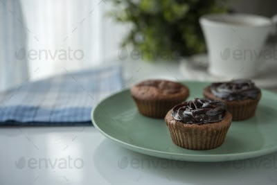 Muffin with chocolate cream next to the window with coffee