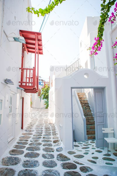 The narrow streets of the island with blue balconies, stairs and flowers in Greece