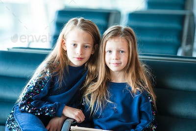 Little adorable girls in airport waiting for boarding near big window