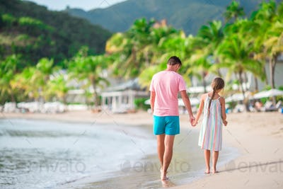 Family at tropical beach walking together on tropical Carlisle bay beach with white sand and