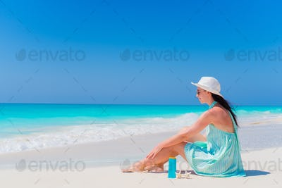 Beautiful young woman with suncream lying on tropical beach