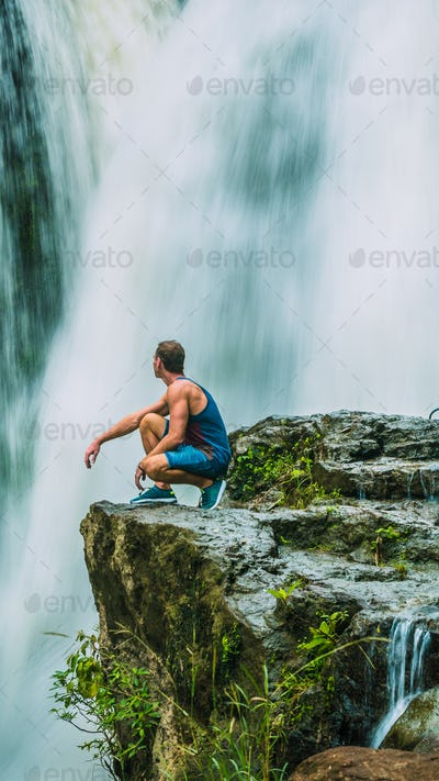 Man sitting in Front of Tegenungan Waterfall near Ubud in Bali, Indonesia