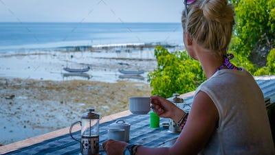 Women with Coffee Cup near Seaweed Algal Plantations - Nusa Penida, Bali