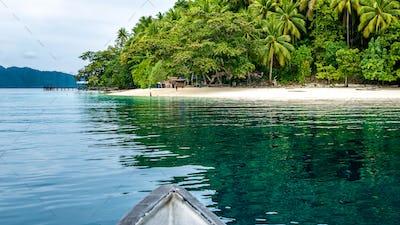 Boat approaching local Village on Friwen Island, West Papuan, Raja Ampat, Indonesia
