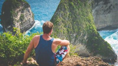 Man on Cliff at Manta Bay or Kelingking Beach, Nusa Penida Island, Bali, Indonesia