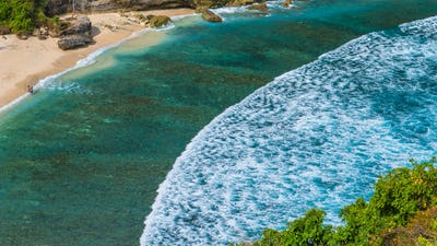 Couple on beautiful Atuh Beach with White Long Waves, Nusa Penida, Bali, Indonesia