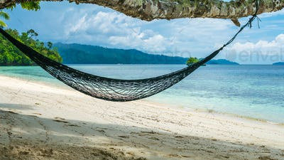 Hammock on the Beach, Batu Lima, Coral Reef of an Homestay Gam Island, West Papuan, Raja Ampat