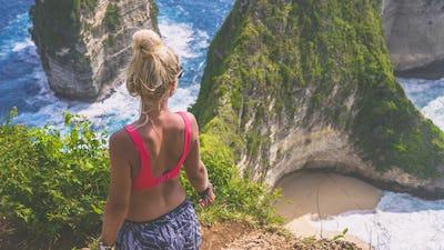 Girl on Cliff at Manta Bay or Kelingking Beach, Nusa Penida Island, Bali, Indonesia