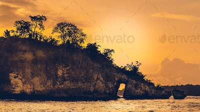 Sunset over the Huge Rock on Beautiful Crystal Bay in Nusa Penida Bali