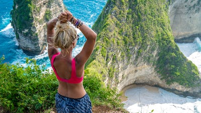 Girl raising her hands on Cliff at Manta Bay or Kelingking Beach, Nusa Penida Island, Bali