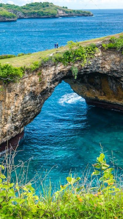 Stone arch over the sea. Broken beach. Rock coastline. Nusa Penida, Indonesia