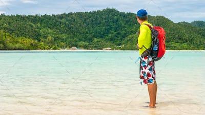 Happy Traveler on White Sand Bank during Low Tide, Kri Island. Raja Ampat, Indonesia, West Papua