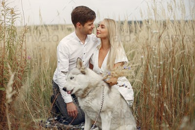 Couple in a autumn field playing with a dog