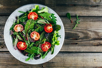 Mix of fresh green salad leaves with arugula, lettuce, spinach, beets and tomatoes