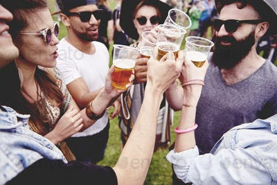 Group of friends drinking a beer at the festival