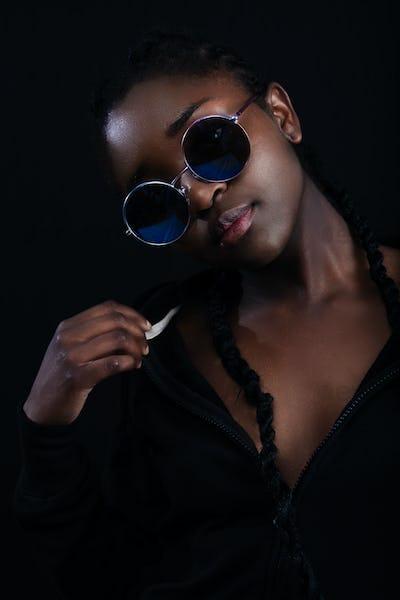 Cool woman with dark skin wearing round sunglasses