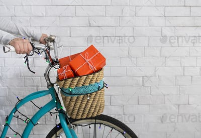 Unrecognizable woman riding a bicycle with Christmas presents