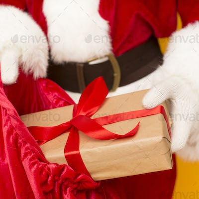 Santa packing his bag with presents and preparing them for delivering