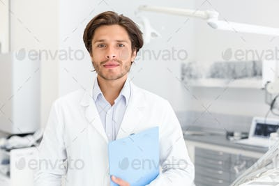 Confident professional dentist holding folder in dental cabinet