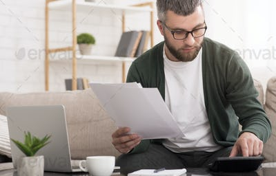 Man with calculator counting money and checking bills at home