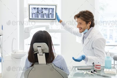 Handsome cheerful dentist doctor demonstrating his patient x-ray results