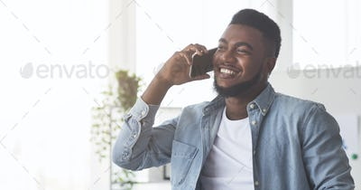 Happy black office worker talking on cellphone and smiling