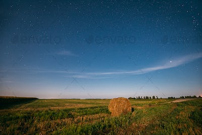 Natural Night Starry Sky Above Field Meadow With Hay Bale After