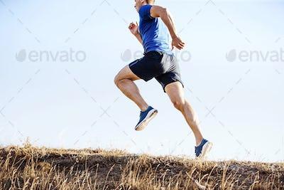 male runner running on mountain trail