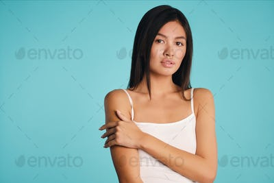 Attractive Asian brunette girl intently looking in camera over colorful background