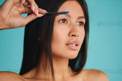Portrait of attractive Asian brunette girl with cosmetic brush thoughtfully applying eyebrow gel